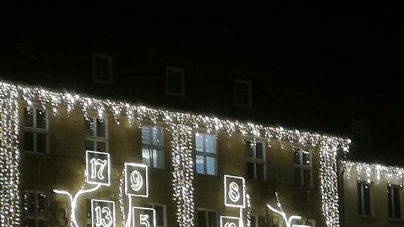 Ein großer, aus Lichterketten geformter Adventskalender an der Fassade der Internationalen Handelskammer in Magdeburg.