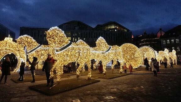 Aus Lichterketten geformte, leuchtende Pferde stehen auf einem Platz.