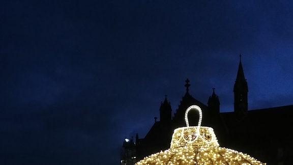 Eine riesige, aus Lichterketten geformte, leuchtende Christbaumkugel steht auf einem Platz. Im Hintergrund die Silouette des Magdeburger Doms.