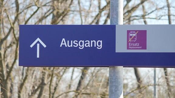 """Auf einem Bahn-Statiosschild steht """"Ausgang"""", dazu ein Richtungspfeil sowie ein Piktogramm für Schienenersatzverkehr"""