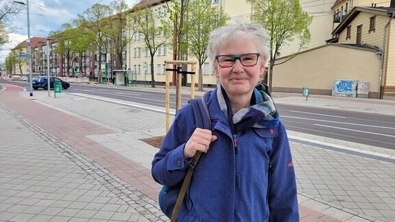 Eine Frau mit einer blauen Jacke und einer bunten Brille steht an einer Kreuzung