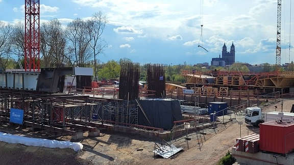 Blick über eine große Baustelle mit neuen Brückenpfeilerfundamenten, Kränen und Fahrzeugen. Im Hintergrund blauer Himmel und die Türme des Magdeburger Doms.