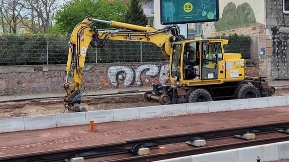 In einem frischen Gleisbett werden neue Schienen verlegt. Dahinter ein gelber Bagger.