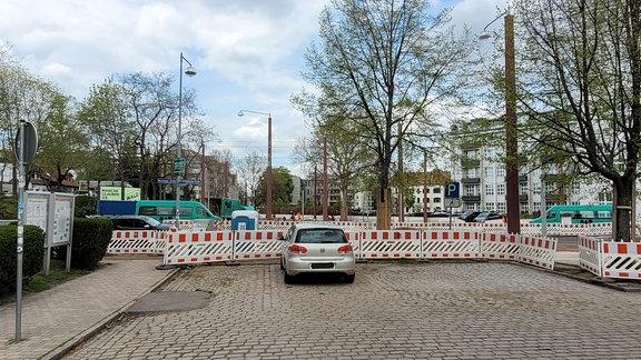 Blick auf eine gesperrte Straßenkreuzung. Davor steht ein Auto geparkt.