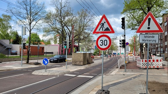 Blick über eine neu wirkende Straße mit integriertem Straßenbahngleis. Am Rand ein Baustellenschild.