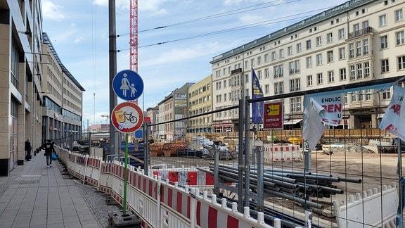 Rechts eine große Baustelle, links ein schmaler Fußweg, der von einem Absperrgitter begrenzt ist.