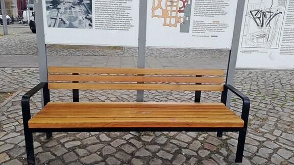 Eine helle Holzbank mit Lehne steht auf dem Magdeburger Domplatz vor einer Infotafel.