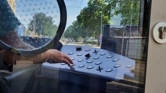 Die Hand eines Straßenbahnfahrers betätigt Knöpfe im Cockpit der Bahn.