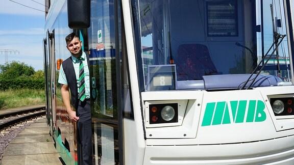 Straßenbahnfahrer steht in der Straßenbahntür.