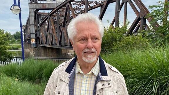 Willi Polte, steht mit einem weißen Anorak und einem karierten Hemd vor der Magdeburger Hubbrücke.