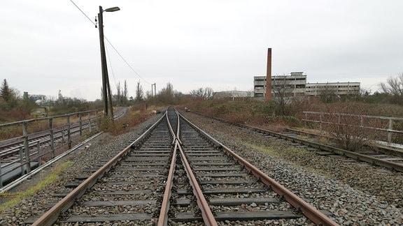 stillgelegte Bahngleise, daneben alte Hallen mit Schornstein