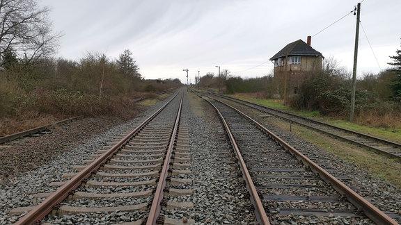 stillgelegte Bahngleise, daneben ein altes Bahnhäuschen