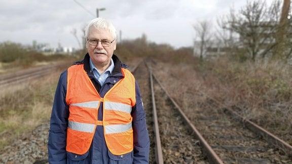 Mann in Warnweste auf stillgelegten Bahngleisen.
