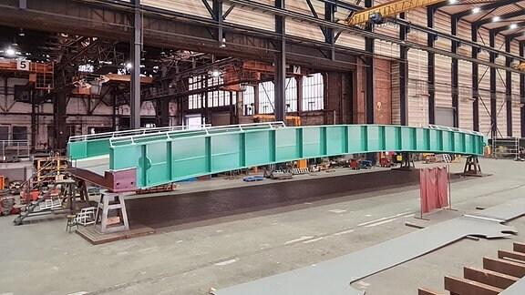 Eine türkisfarbene Brücke steht in einer Halle
