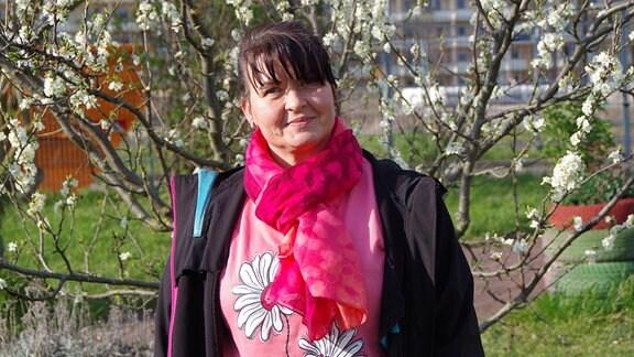 Eine dunkelhaarige Frau steht vor einem blühenden Busch und guckt freundlich in die Kamera.