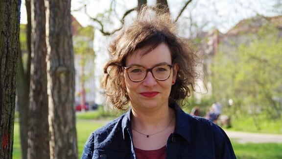 """Diana Lösch, für die Fraktion """"Die Linke"""" im Stadtrat in Magdeburg, steht mit vom Wind verwehten Haaren in einem Park und schaut in die Kamera."""