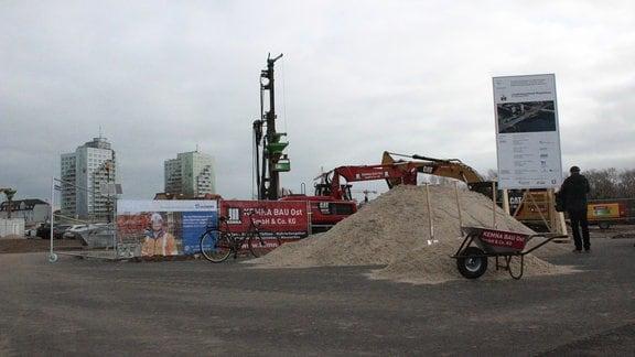 Haufen Sand mit Schubkarre und Baugeräte und zwei Hochhäuser im Hintergrund