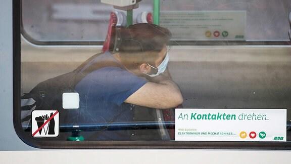 Ein Mann sitzt mit Mundschutz und Handy in einer Strassenbahn in Magdeburg