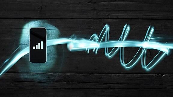 Ein Handy vor einem dunklen Holzhintergrund.