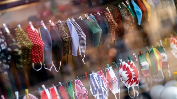 Stoffmasken im Schaufenster einer Schneiderei
