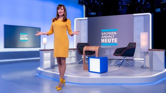 Eine Frau in einem gelben Kleid steht im neuen Studio von MDR SACHSEN-ANHALT HEUTE.