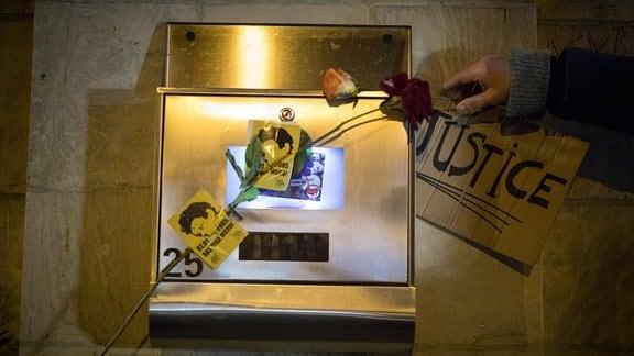 Blumen, Aufkleber und ein Pappschild mit Aufschrift 'Justice' in Gedenken an Oury Jalloh