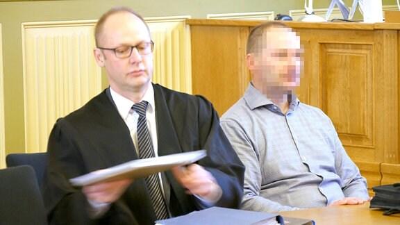 Ein Mann sitzt neben seinem Anwalt.