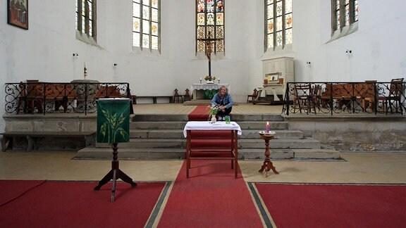 Eine junge Frau sitzt auf den Stufen im Altarraum einer Kirche.