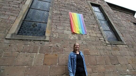 Eine junge Frau steht unter einer Regenbogenflagge an einer Kirchenmauer.