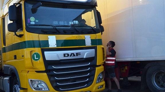 Ein Mann spricht mit einem Lasterfahrer, der aus seinem Fenster hinunterschaut.
