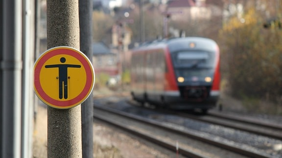 Ein Durchgang verboten-Schild steht am Ende eines Bahnsteiges an den Gleisen. Ein roter Zug (VT 642) kommt angefahren.