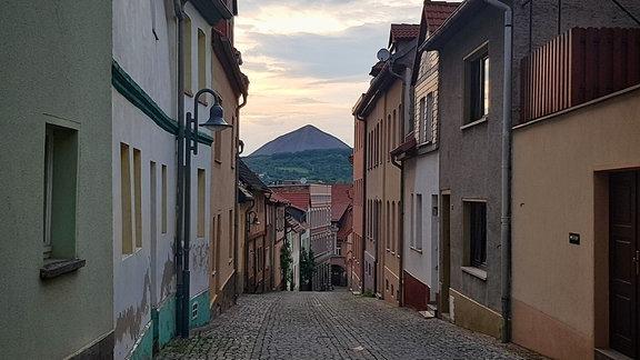 Eine Gasse, rechts und links Häsuer, am Horizont ein Berg