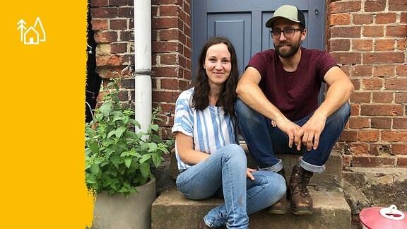 Eine junge Frau mit Jeans und Bluse und ein Mann mit Sonnenbrille und Cappy sitzen auf einer Treppenstufe vor einer blauen Haustür.