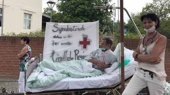 """Ein gestellter Wagen mit einem Mann im Krankenbettt und einer gestellten Krankschwester vor ihm sowie der Aufschrift """"Symbolisch stehen wir hier für unsere ländliche Region"""" auf einem Banner."""