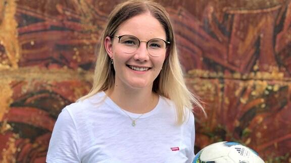 Blonde junge Frau mit Fußball in weißem T-Shirt