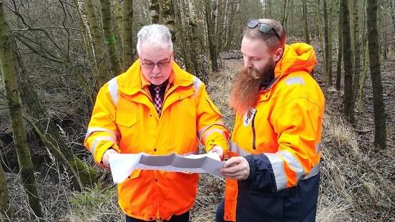 Zwei Männer in orangenen Warnjacken stehen im Wald und schauen in eine Karte