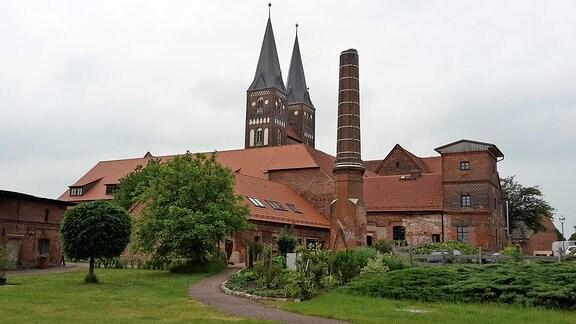 Blick auf das Kloster Jerichow mit den Doppeltürmen der Stiftskirche und dem Schornstein der alten Ziegellei.