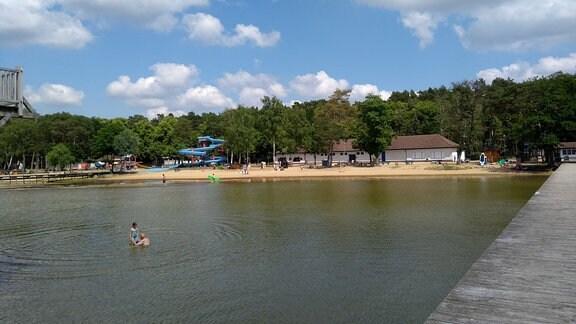 Blick von einem hölzernen Bootsstreg auf ein Strandbad