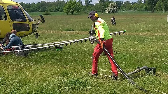Zwei Leute arbeiten an Sprühvorrichtung von Helikopter, der auf einer Wiese steht, ein Mann kommt mit Schlauch dazu