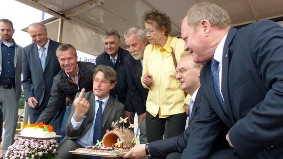 Bundesverkehrsminister Andreas Scheuer, Ministerpäsident Reiner Haselof und Landeverkehrsminister Thomas Webel mit der Brückentorte