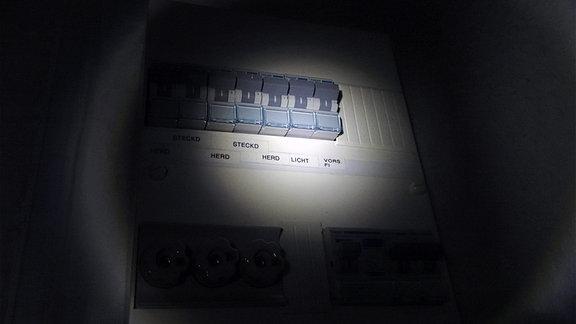 Sicherungskasten bei Stromausfall im Taschenlampenlicht.