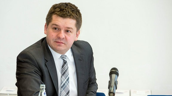 Sven Schulze, ein Mann in Sakko und Krawatte lehnt sich mit seinem Ellbogen auf einen Konferenztisch