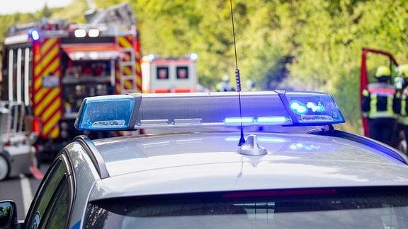Bei einem Verkehrsunfall stehen Fahrzeuge der Rettungskräfte vor Ort.