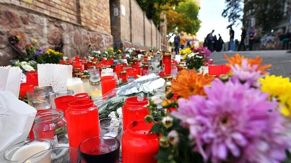Blumen und Kerzen stehen neben der Tür zur Synagoge in Halle