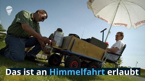 Männer zapfen ihr Bier vom Bollerwagen