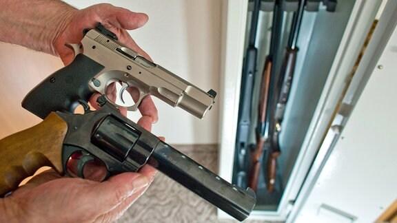 Ein Sportschütze zeigt 2009 eine Pistole und einen Revolver vor einem Waffenschrank mit drei Gewehren in einem privaten Haushalt.