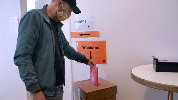 Ein Mann mit Maske steckt seine Briefwahlunterlagen in eine Wahlurne.