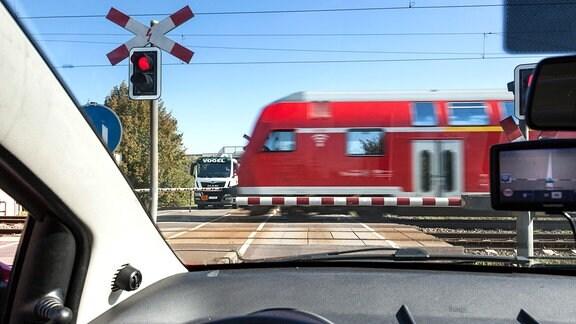Blick aus einem Pkw an einem beschrankten Bahnübergang, den ein Regionalzug passiert