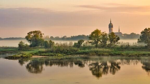 Sonnenaufgang an der Elbe mit Blick auf ein Türmchen von Wittenberg