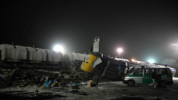 Polizeifahrzeug neben zerstörtem Zug